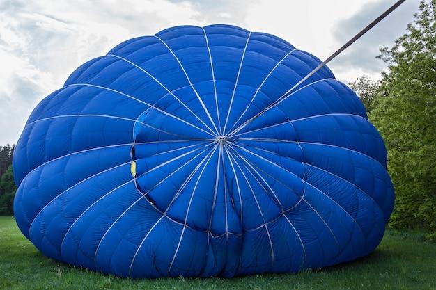 Um balão com uma cesta repousa no chão equipamento para encher o balão com frio e calor