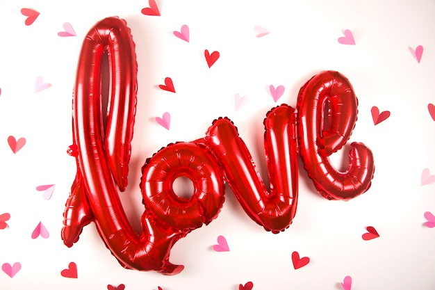 Um balão em forma da palavra amor em branco ao lado de pequenos corações de dia dos namorados.