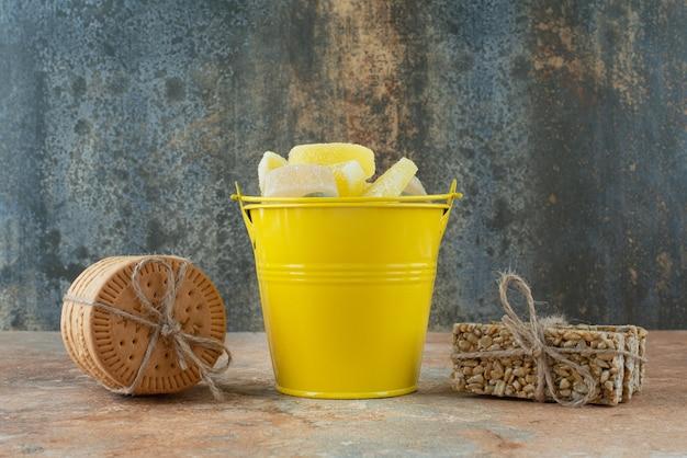 Um balde amarelo de geleia com biscoitos e pedaços de amendoim