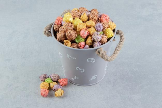 Um balde cheio de pipocas doces multicoloridas.