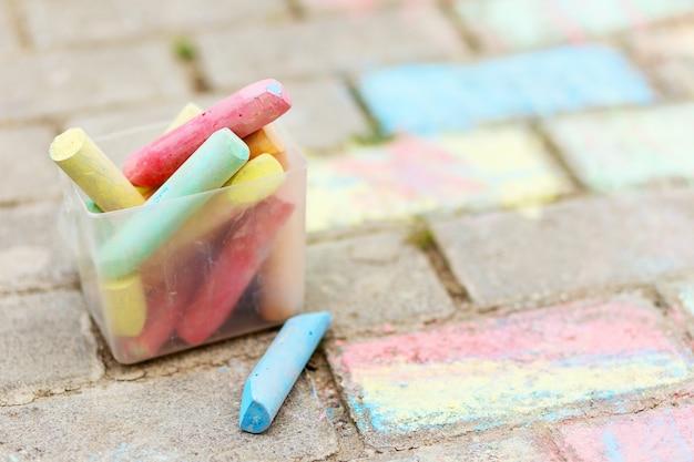Um balde de giz colorido no asfalto em caixa de plástico. desenhar com giz na calçada. lápis multicoloridos para desenhar.