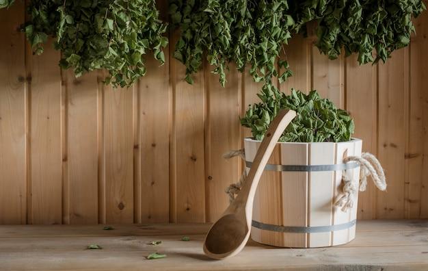 Um balde de madeira e uma vassoura de bétula em um banho russo. sauna.