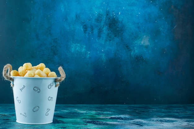 Um balde de palitos de milho na mesa de mármore.
