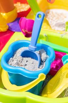 Um balde infantil cheio de areia com uma pá presa na areia.