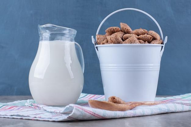 Um balde metálico cheio de pastilhas de chocolate saudáveis cobrem os flocos de milho com uma jarra de vidro com leite.