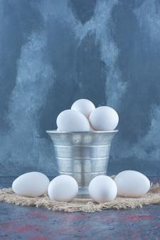 Um balde metálico com ovos de galinha crus frescos.