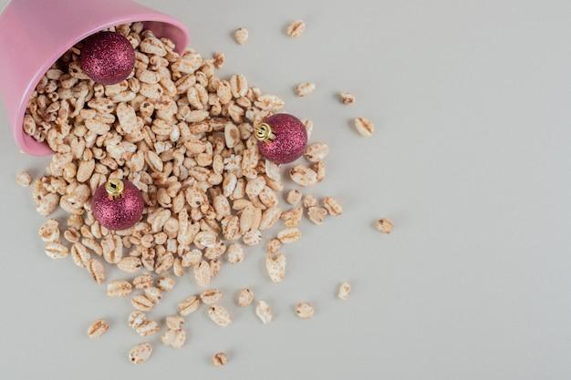 Um balde rosa cheio de cereais saudáveis com bolas de natal.