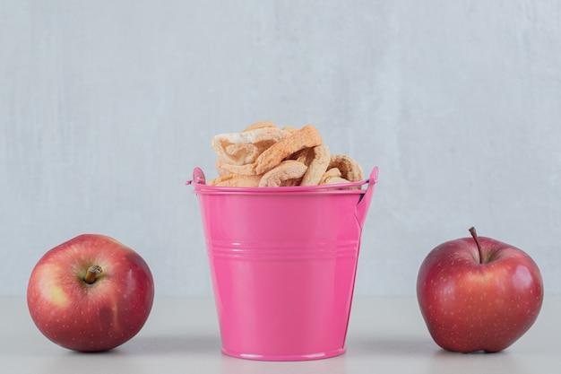 Um balde rosa cheio de maçã seca com duas maçãs frescas.