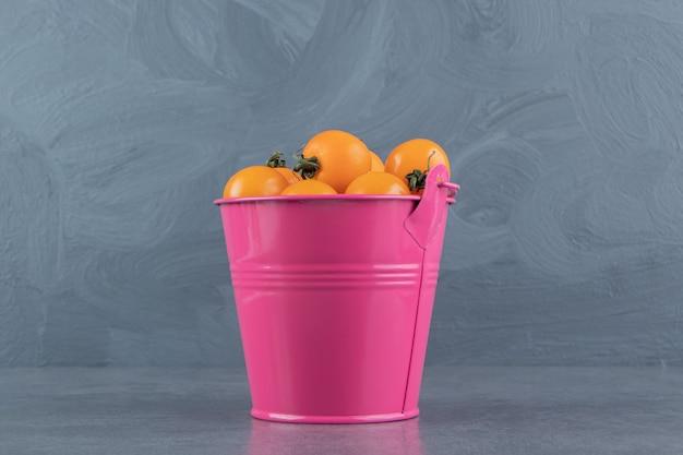Um balde rosa cheio de saboroso tomate cereja maduro