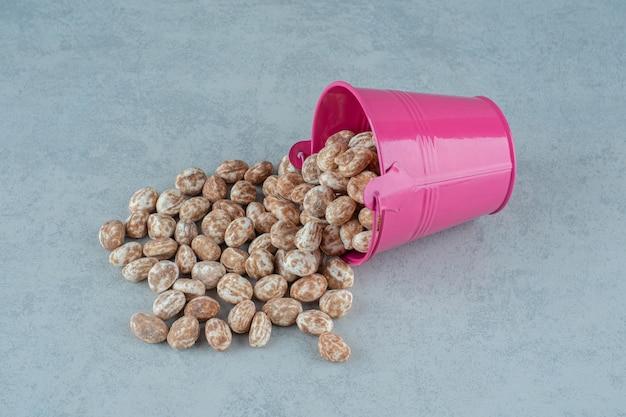 Um balde rosa cheio de um delicioso pão de mel doce na superfície branca