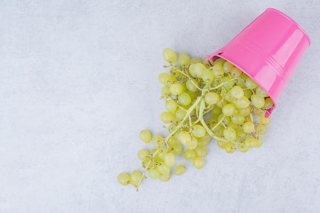 Um balde rosa cheio de uvas verdes doces. foto de alta qualidade