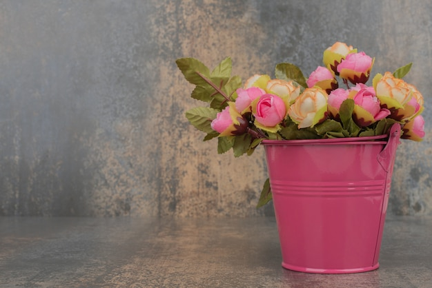 Um balde rosa com buquê de flores na superfície de mármore.