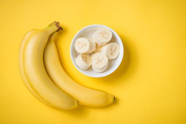 Um banch de bananas e uma banana fatiada em um prato sobre fundo amarelo.