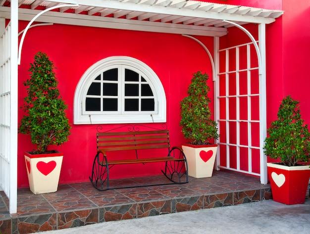 Um banco decorado na frente da casa para relaxar.