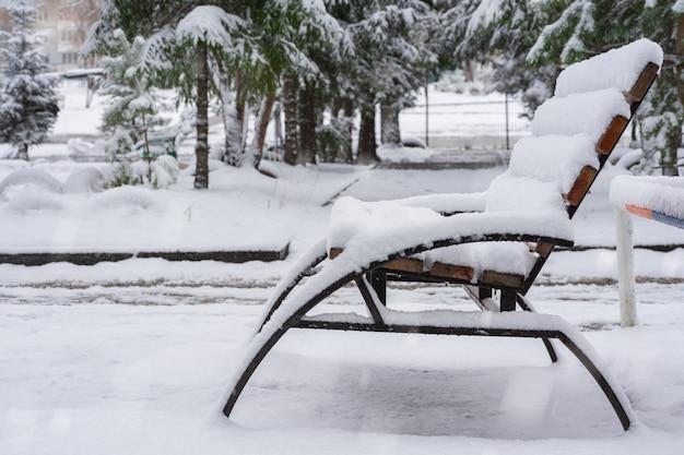 Um banco solitário fica em um parque de neve da cidade durante uma queda de neve no inverno.