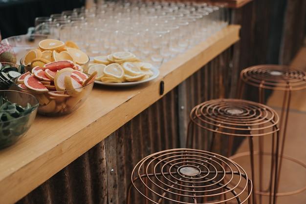 Um bar de bebidas com bancos de metal muito modernos. no bar há algumas taças com laranjas, toranjas, limões e copos para bebidas.