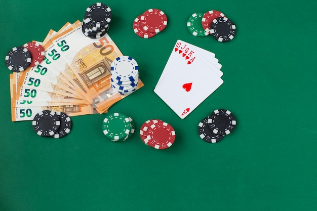 Um baralho de cartas em forma de leque, notas de euro e fichas de jogo