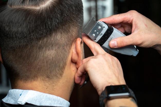 Um barbeiro faz um corte de cabelo