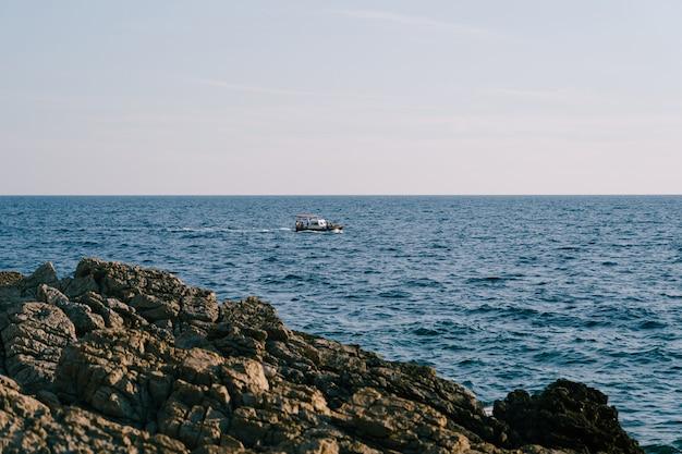 Um barco a motor com toldo e turistas surfam as ondas do mar perto da costa rochosa