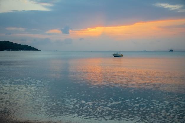Um barco à vela com pôr do sol nebuloso e reflexo na água /