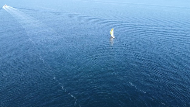 Um barco à vela navega em mar aberto. drone aéreo de uma visão panorâmica de um lindo barco à vela branco navegando em mar aberto.