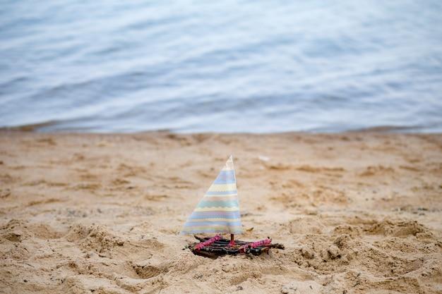 Um barco de brinquedo em uma praia arenosa, um veleiro de brinquedo na areia contra o mar