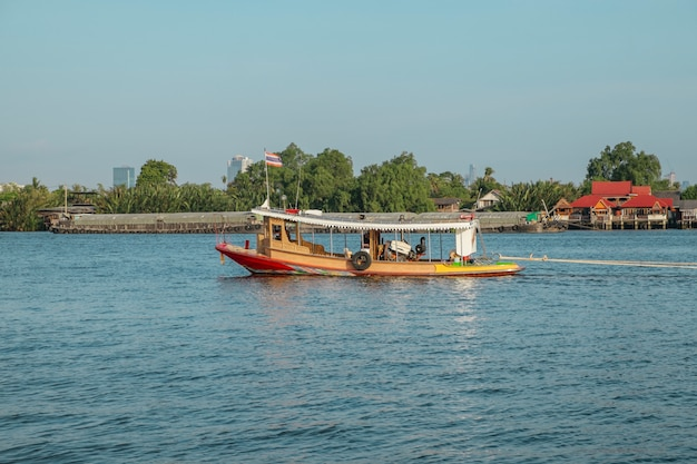 Um barco de madeira local com a bandeira tailandesa no rio de chao phraya, tailândia.