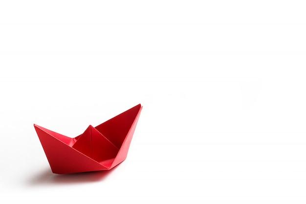 Um barco de papel vermelho sobre uma superfície branca brilhante. copie o espaço