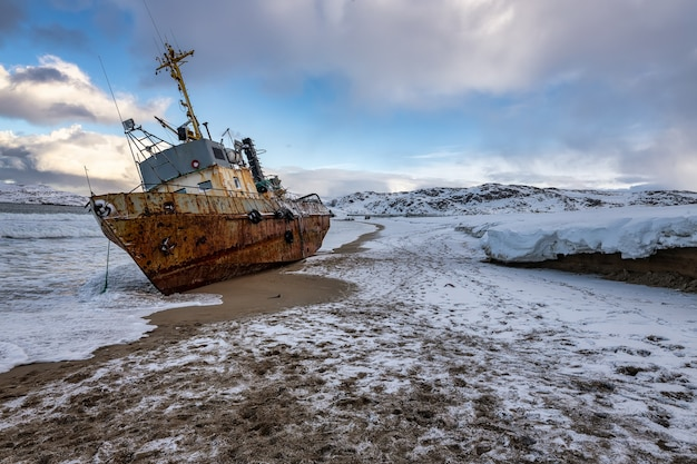 Um barco de pesca caído de lado, teriberka, rússia