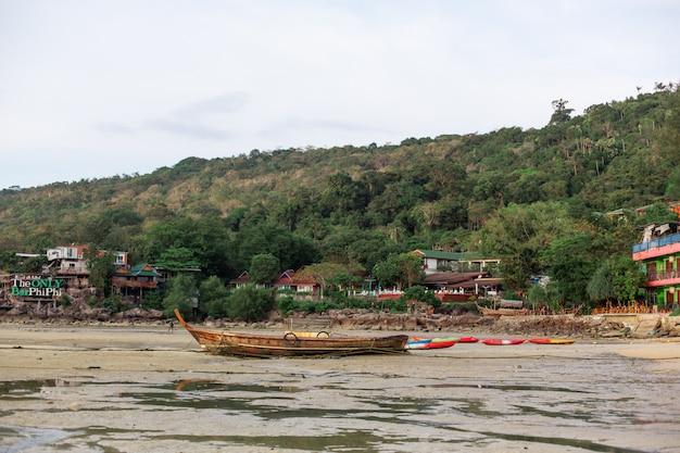 Um barco de pesca de madeira estava no fundo arenoso do oceano na maré baixa,