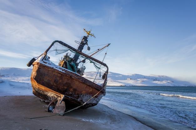 Um barco de pesca deitado de lado, o mar de barents, a península de kola, teriberka, rússia