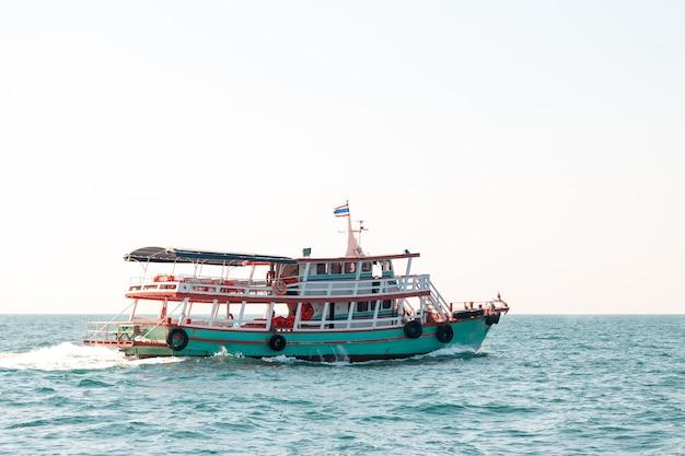 Um barco leva turistas a uma ilha no mar na tailândia.