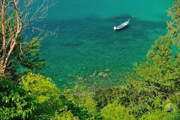 Um barco longtail tradicional flutua na água azul esmeralda cristalina perfeita. phuket, tailândia