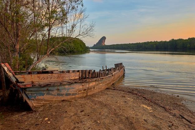 Um barco naufragado em uma margem do rio krabi em uma manhã