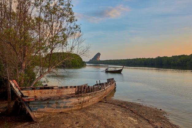 Um barco naufragado em uma margem do rio krabi.
