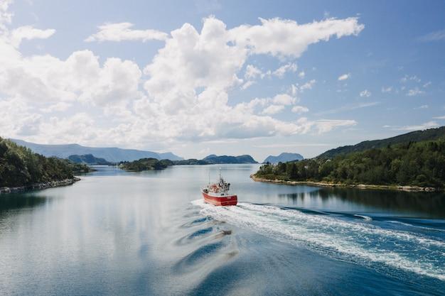 Um barco no corpo da água cercado por árvores sob um céu azul claro com nuvens brancas