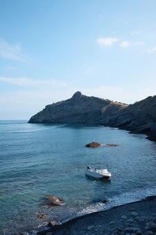 Um barco solitário atracado em uma costa de pedra, ao redor do mar e das montanhas, uma praia rochosa, uma paisagem marinha