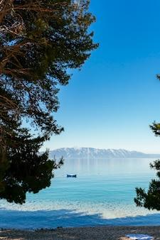 Um barco solitário flutuando no lago com a montanha na distância contra o céu azul claro