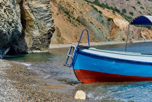 Um barco vazio na ressaca do mar perto das rochas.