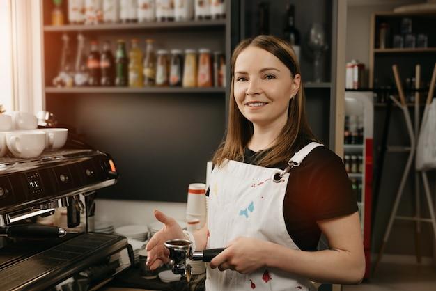 Um barista com avental branco sorri e posa segurando uma calcadeira de metal e um porta-filtro com café