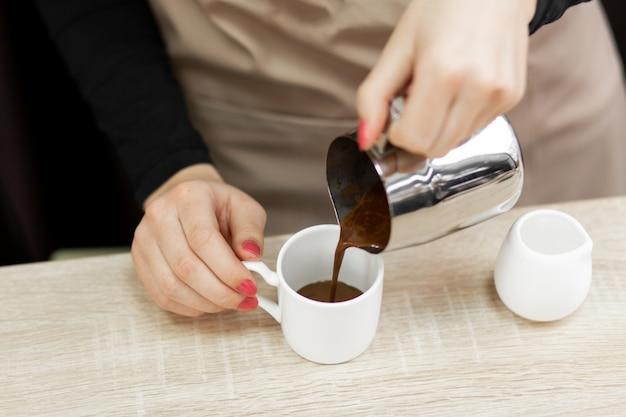 Um barista de avental derrama chocolate quente em uma xícara.