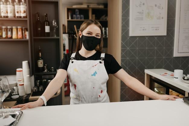 Um barista feminino em uma máscara de rosto preto médica sorri e espera por clientes no café