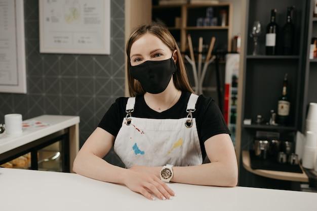 Um barista feminino feliz em uma máscara protetora preta médica sorri e espera por clientes na cafeteria. uma bela dona do café posa com os braços cruzados atrás do bar.