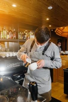 Um barista mascarado prepara um delicioso café no bar de uma cafeteria. o trabalho de restaurantes e cafés durante a pandemia. Foto Premium