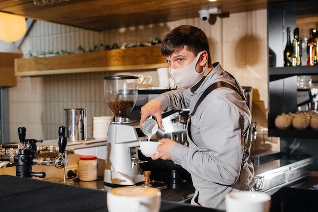 Um barista mascarado prepara um delicioso café no bar de uma cafeteria