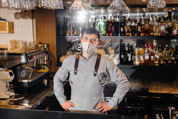Um barman estiloso de máscara e uniforme durante uma pandemia. o trabalho de restaurantes e cafés durante a pandemia.