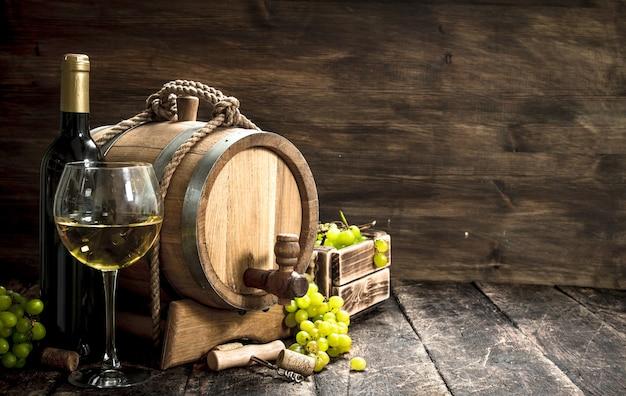 Um barril de vinho branco com ramos de uvas verdes.