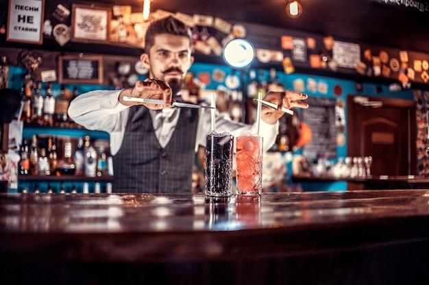 Um bartender confiante adiciona ingredientes a um coquetel atrás do balcão
