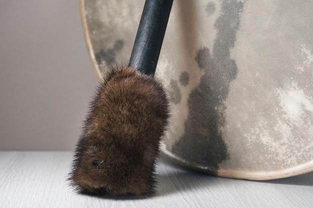 Um batedor de pele fica ao lado do pandeiro do xamã.