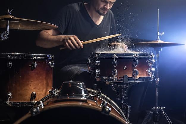 Um baterista toca baquetas em uma caixa com salpicos de água em um quarto escuro.
